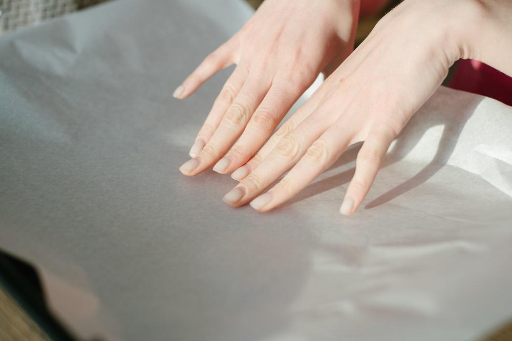 женские руки застилают противень пергаментом