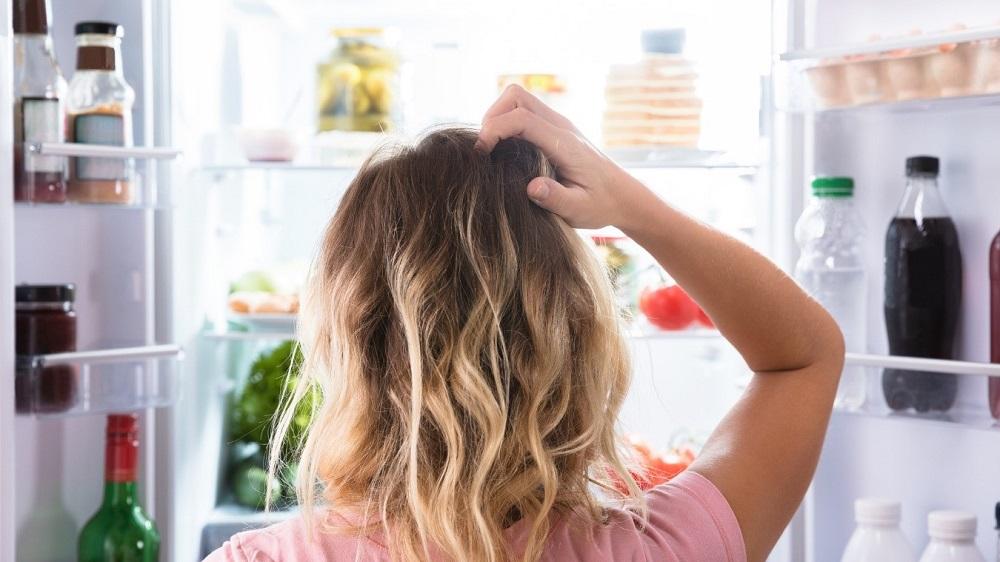 женщина стоит возле холодильника