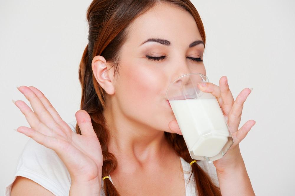 молодая женщина пьет молоко