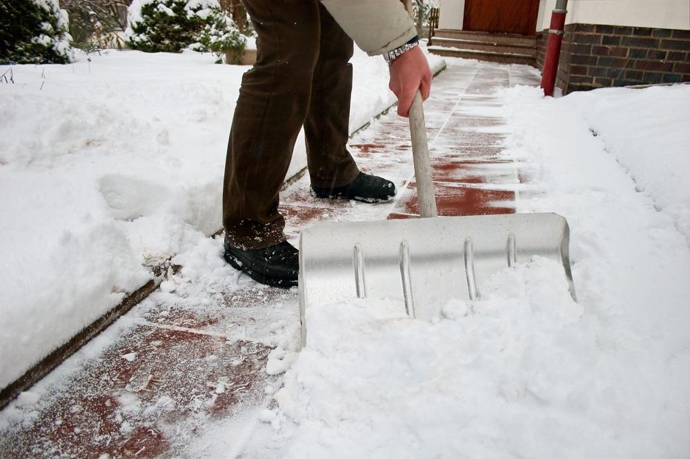 мужчина расчищает снег