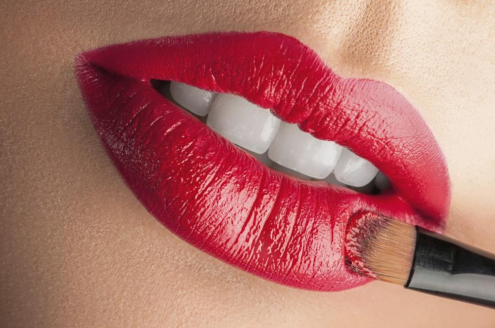 девушка красит губы кистью