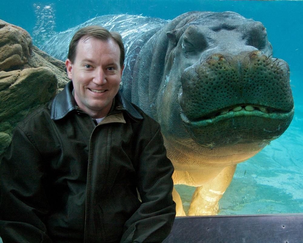 мужчина фотографируется с бегемотом