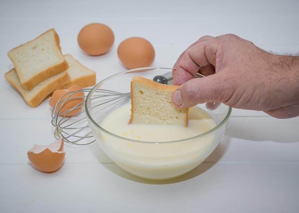 мужчина макает хлеб в молоко