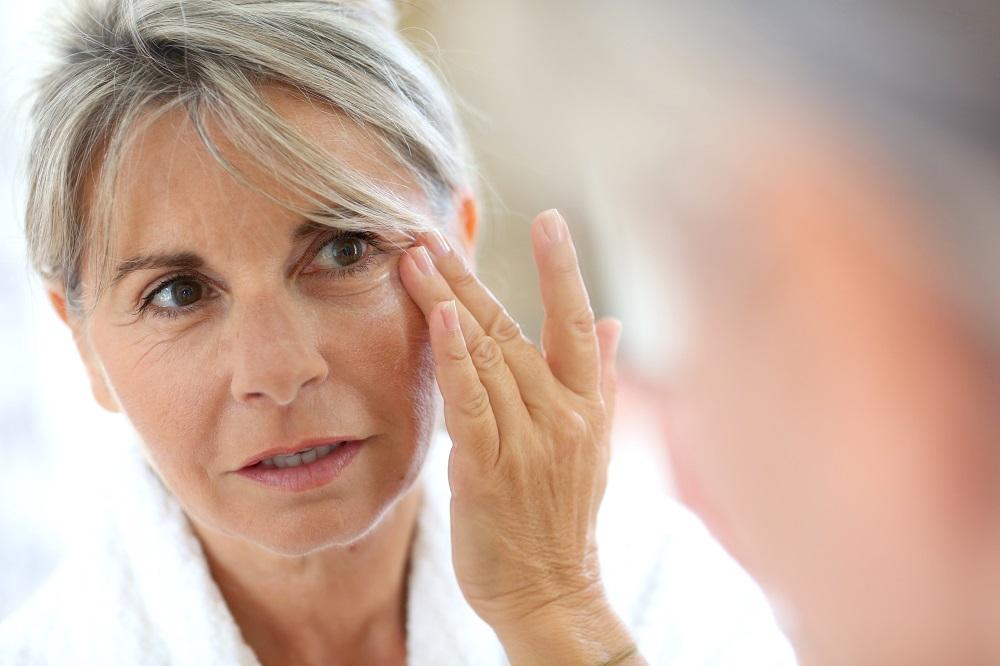 женщина наносит крем от морщин